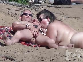 Le hace una mamada a su esposo en medio de una playa nudista